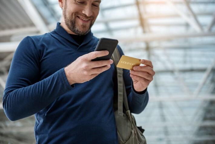 Executivo com cartão e celular nas mãos