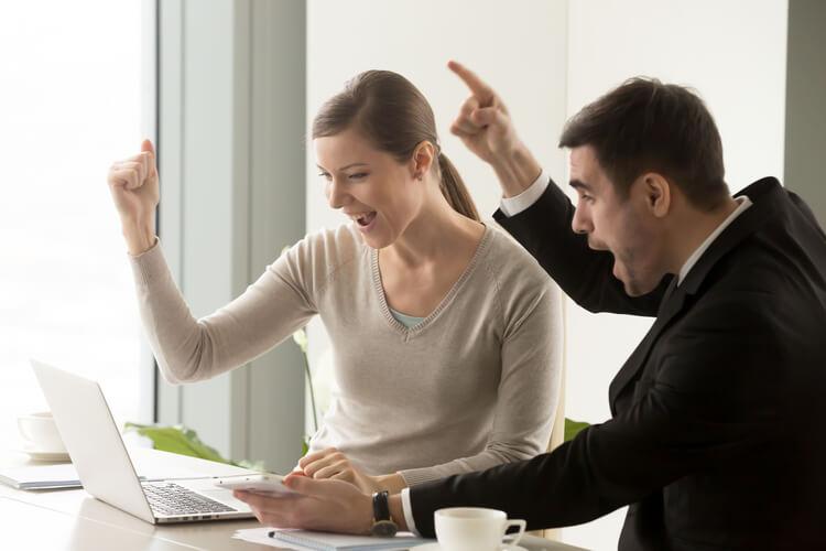 Duas pessoas em frente a laptop comemorando com uma mão para cima