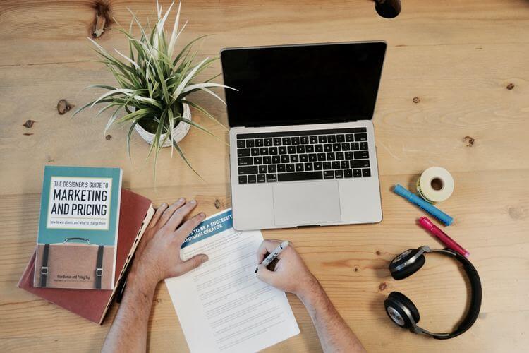 Superfície com laptop livro de marketing e mãos realizando anotações