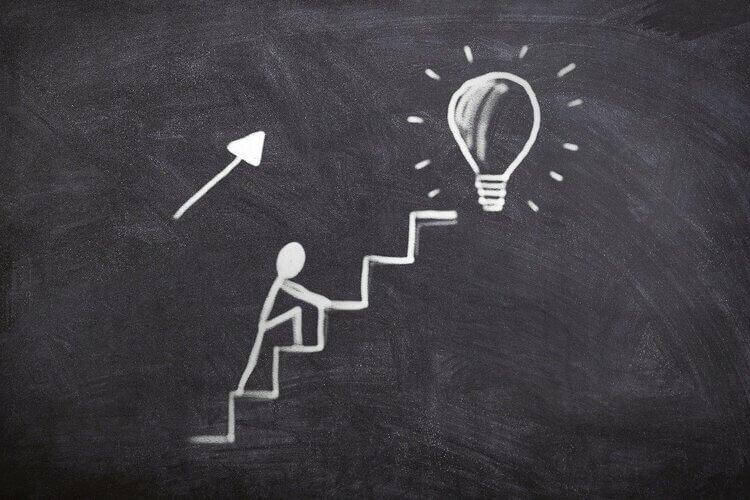 Desenho em giz de pessoa escalando uma escada em direção a uma lampada iluminada no quadro negro