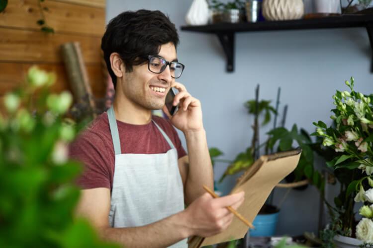 Homem lojista falando ao telefone