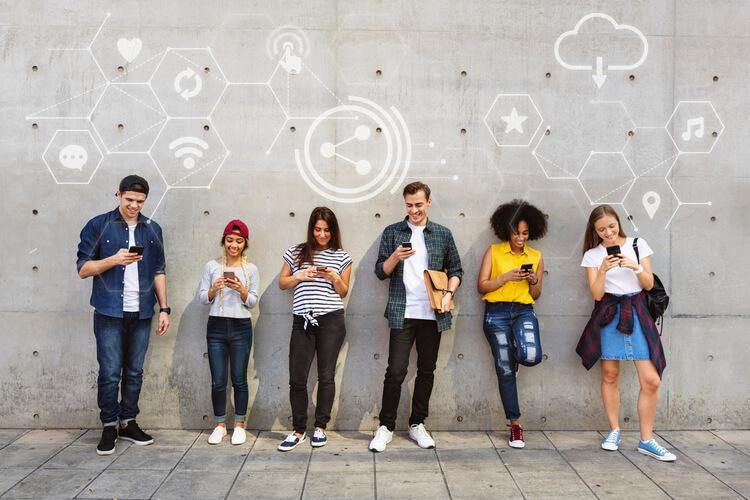 Jovens enfileirados manuseando smartphone